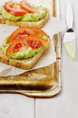 Avocado cream with toasts and tomatoes on a rustic surface