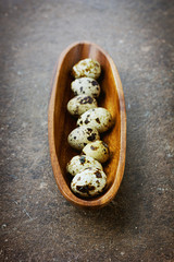 Quail eggs in a wooden cup on a vintage surface