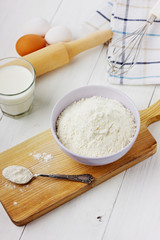 Flour in ceramic bowl with eggs and rolling pin
