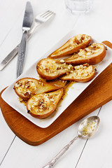 Dessert from the baked pears with honey and nuts in plate