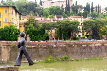 Sculpture of a man walking from the bridge into the river Arno