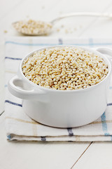 Pearl barley in a white ceramic bowl on a wooden surface
