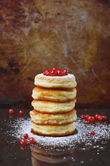 Curds fritters with icing sugar and cranberries