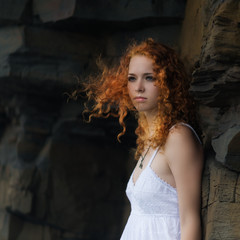 Portrait of a beautiful redhead woman in a white dress.