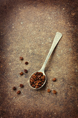 Coffee beans in a spoon on a vintage board