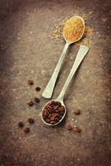 Coffee beans and brown sugar in a spoon on a vintage surface