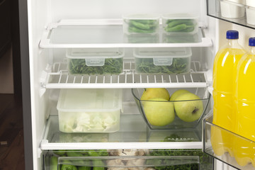 Fruits and vegetables in two containers in a modern fridge - a h