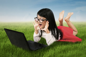 Amazed girl with laptop on field