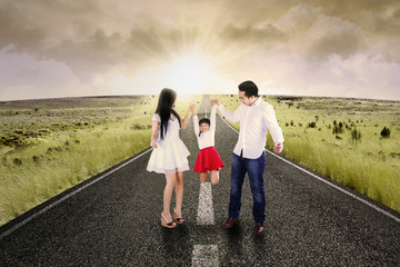 Attractive family playing on the road