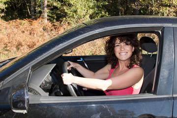femme qui attend et qui rit dans sa voiture