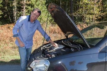 Homme souriant devant sa voiture en panne