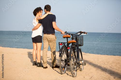 canvas print picture Paar mit Fahrrädern auf einem Stadtstrand