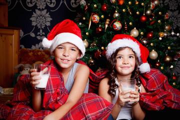 Sweet little kids drinking milk before sleeping