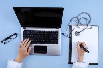 Closeup of doctor hands using laptop