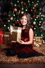 Portrait of a beautiful little girl holding a Christmas present