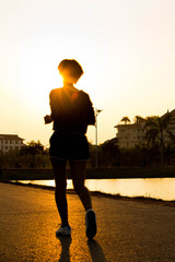 Runner athlete feet running on road. woman fitness silhouette su