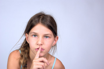 Young girl with finger on lips shushing