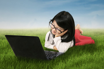 Cute girl with laptop on meadow