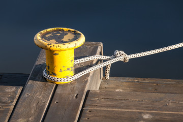Yellow mooring bollard with nautical rope on pier