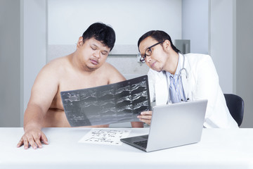Doctor showing x-ray to overweight person