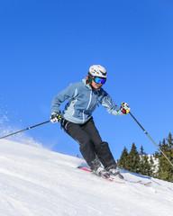 Skifahrerin schwingt auf der Piste
