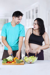 Expectant mother and husband prepare salad