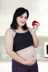 Expectant woman eating a red apple