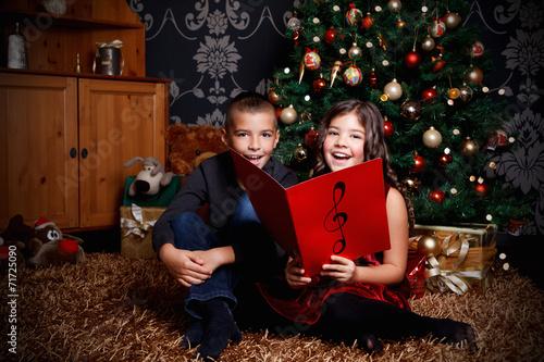Leinwanddruck Bild Little children singing a song at Christmas Eve