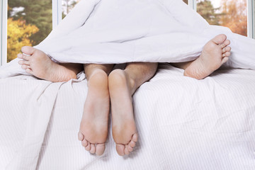 Feet of couple having sex in bed