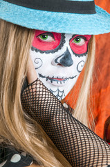 Girl with Calavera Mexicana makeup mask in the hat. Helloween