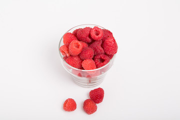 Glass Cup of Red Raspberries with Three on Counter