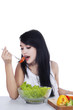 Pretty woman eats a bowl of salad