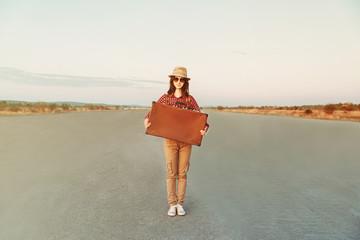 Hipster girl traveler holds retro suitcase
