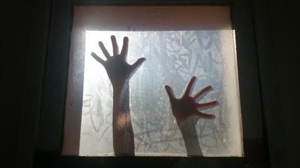 Silueta de manos en ventana