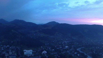 Red sunset over  village in mountain valley. Aerial  panorama