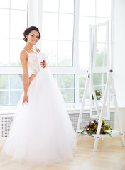 Beautiful bride-to-be trying her dress in shop