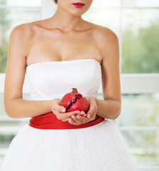 Pomegranat in hands of a bride