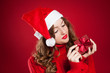 girl in red sweater holding Christmas present wearing Santa Clau