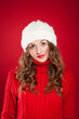 beautiful girl with curly hair wearing warm hat and red sweater