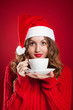 beautiful brunette girl in Santa Clause hat holding white mug