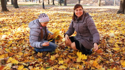 mother with her daughter scatter yellow leaves in autumn park