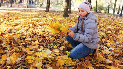 cute teen girl sits on her knee and collects yellow leaves