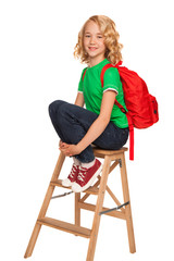 little blonde girl in green t-shirt with red bag
