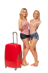 two girls wearing jeans shorts with big red suitcase