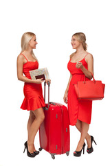 two girls wearing red dresses with big suitcase and bag