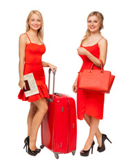two blonde girls wearing red dresses with big suitcase and bag