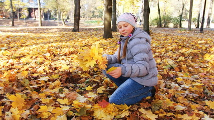 teen girl sits and collects yellow leaves falling from trees