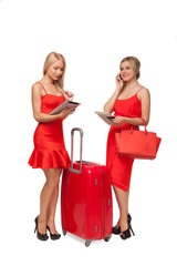 two girls wearing red dresses with big suitcase and bag and tabl