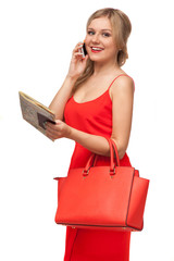woman in red dress holding bag and map talking on the cell phone