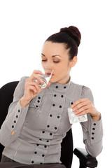 businesswoman with headache holding pills